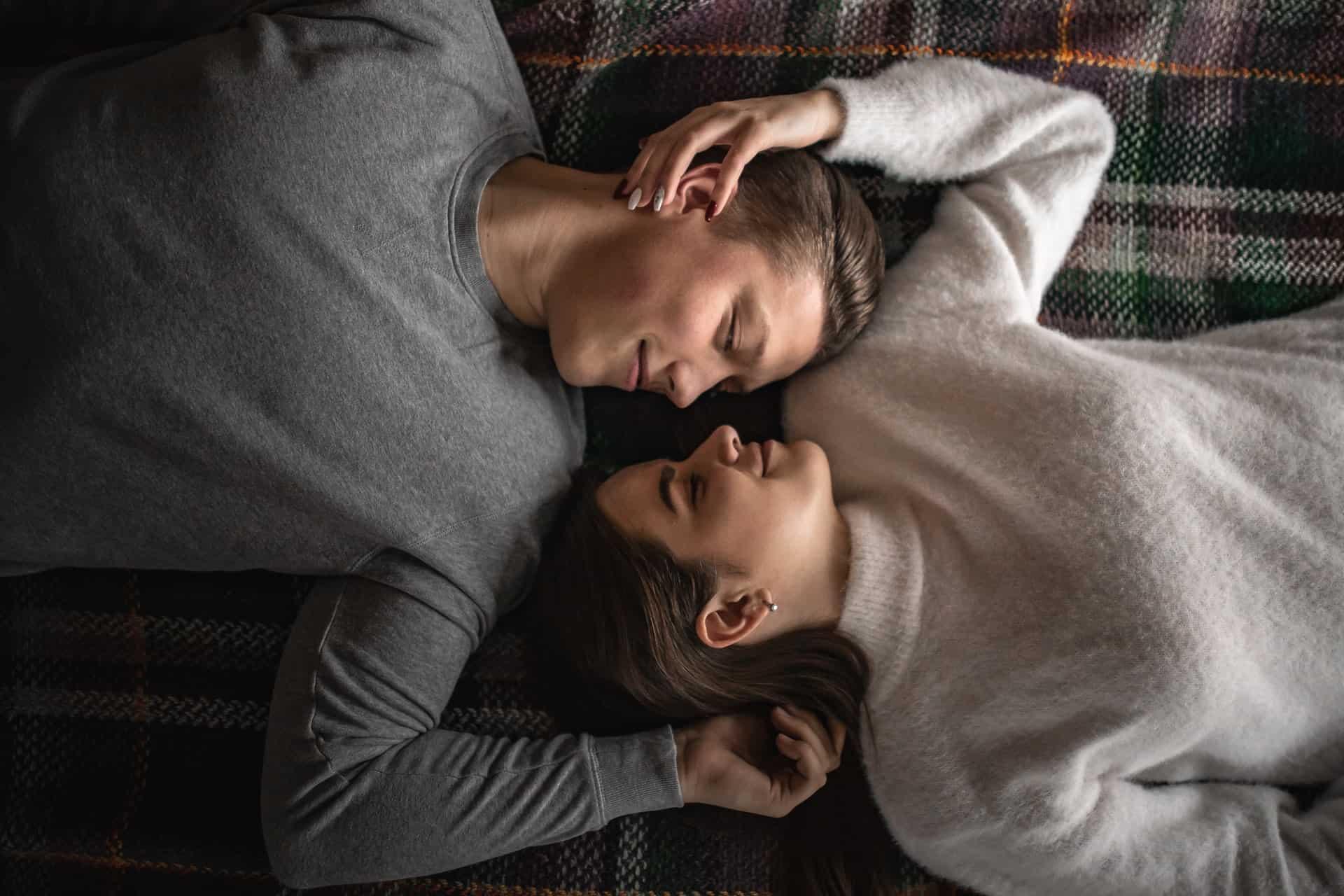 un homme et une femme sont allongés sur le sol