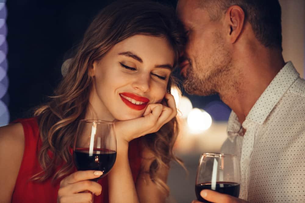 un homme sent les cheveux d'une femme en buvant du vin