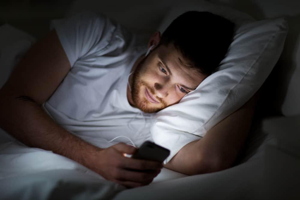 un homme touche au téléphone en position couchée dans son lit