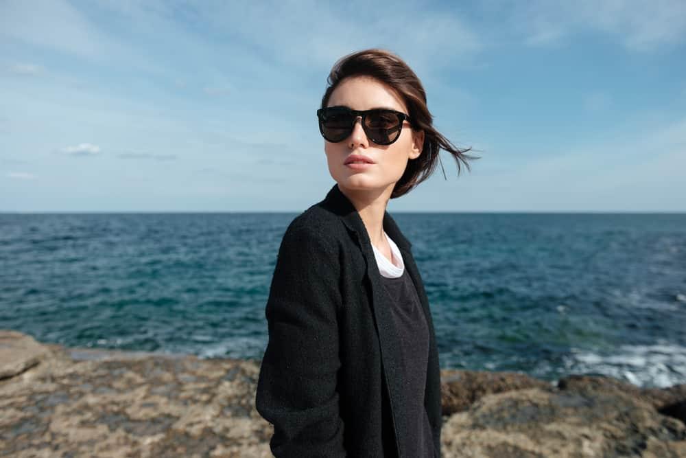 une femme avec des lunettes se tient au bord de la mer
