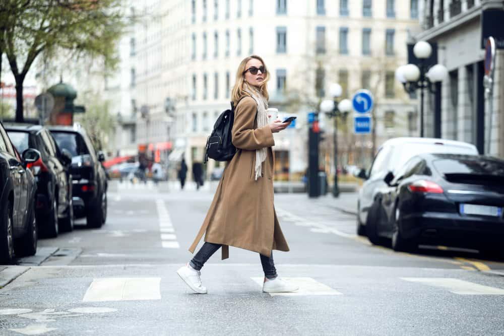 une femme avec un long manteau marche dans la rue
