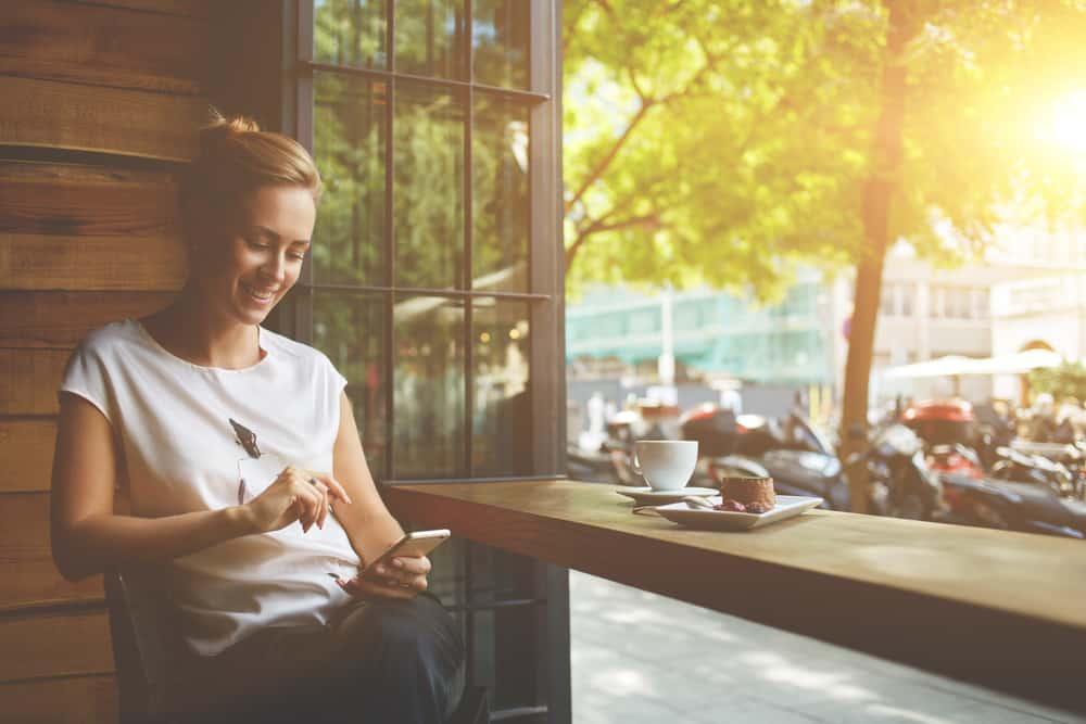 une femme est assise dans un café et tape au téléphone