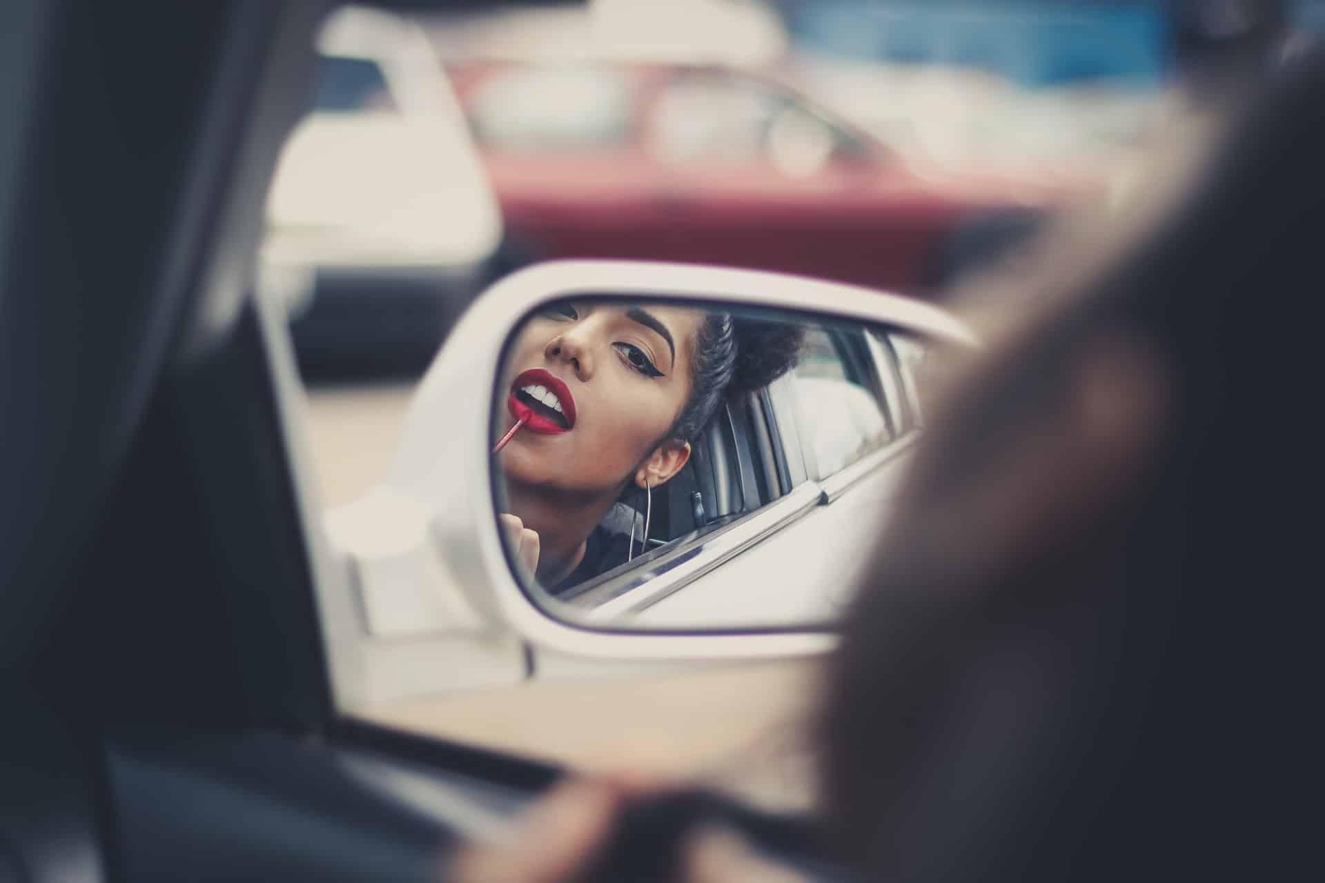 une femme fixe le rouge à lèvres dans une voiture