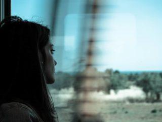une femme triste voyage en train et regarde par la fenêtre