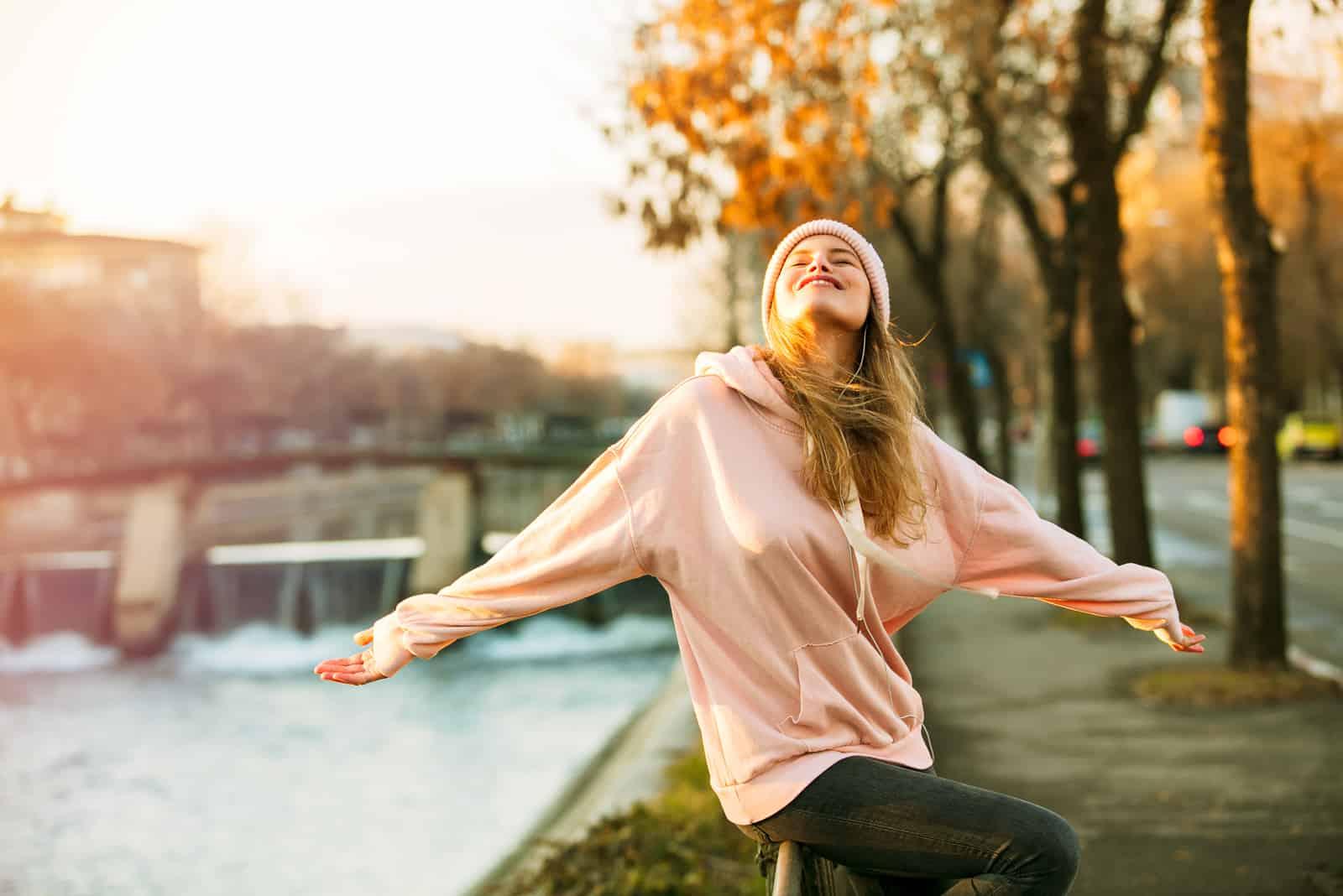 Au coucher du soleil, une blonde heureuse dans un sweat à capuche rose est assise sur une clôture au bord de la rivière
