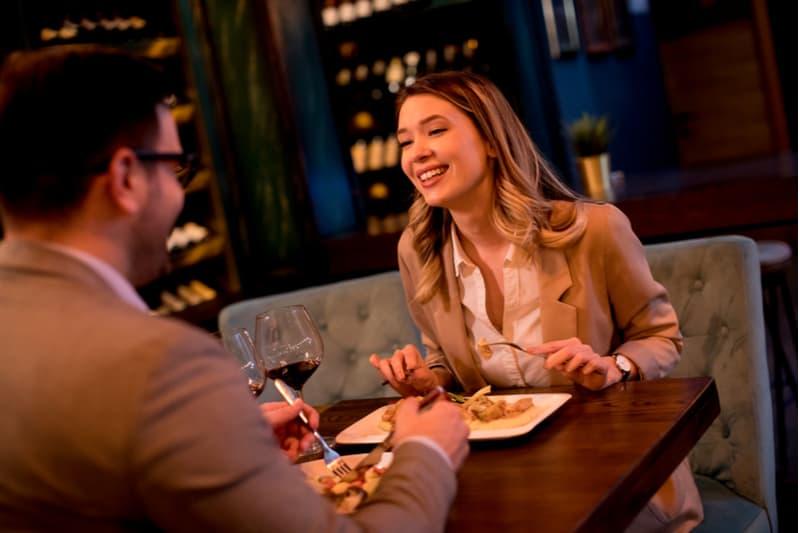 Beau jeune couple en train de dîner au restaurant et de boire du vin rouge