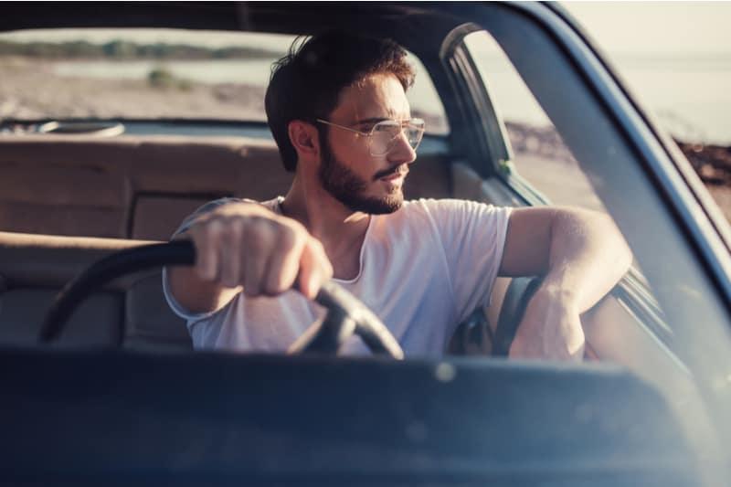 Bel homme barbu est assis dans sa voiture rétro verte
