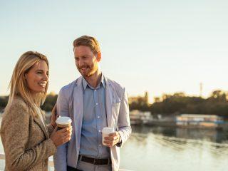 un homme et une femme debout et buvant du café
