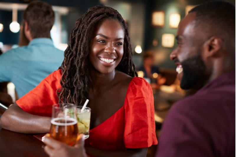 Couple sur date assis au comptoir du bar et parler