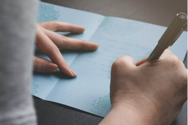 Dame écrivant une carte fabriquée à la main à la famille ou à un ami
