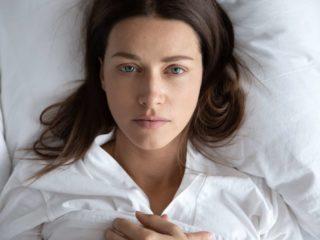 femme triste couchée dans son lit et penser