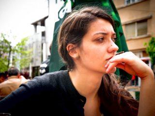 la brune s'assoit sur la terrasse du café et pense