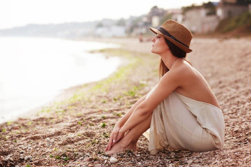 Femme calme assise seule sur une plage de sable en soirée