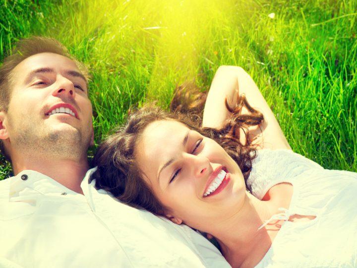 un homme et une femme s'allongent sur l'herbe et rient