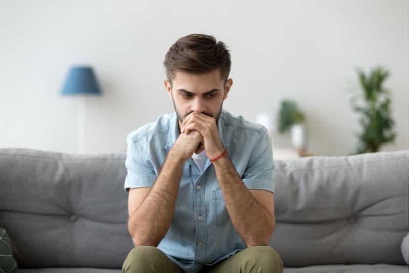 Homme sérieux assis sur le canapé seul à la maison