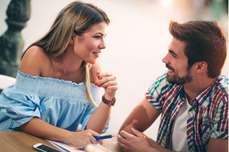 Jeune couple assis dans un café à parler et profiter de la première date