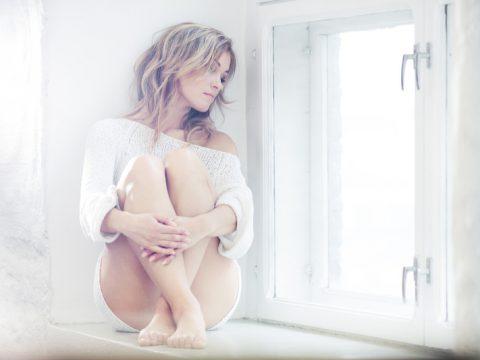 une femme triste est assise près de la fenêtre