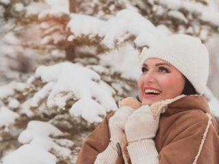 une belle femme souriante debout dehors dans la neige