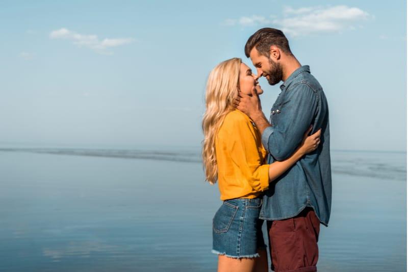Petite amie souriante et petit ami touchant avec le nez sur la plage