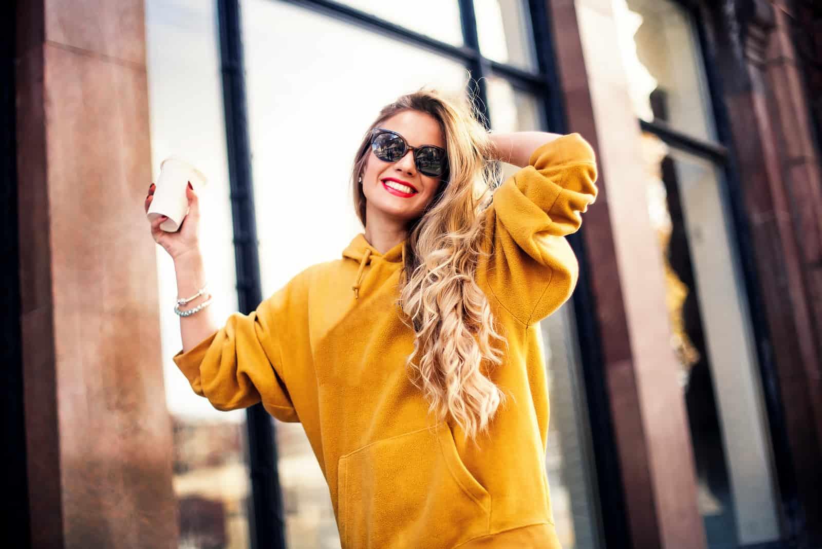 Une femme aux longs cheveux blonds se tient avec du café à la main