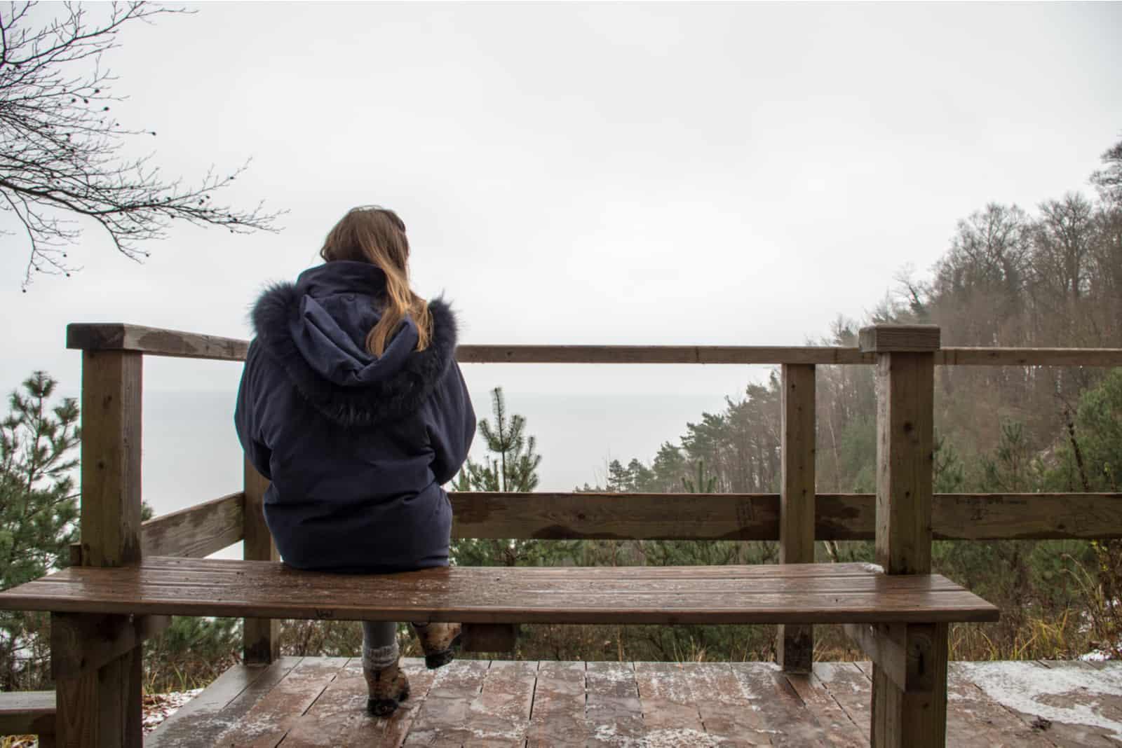 Une femme aux longs cheveux bruns attachés en queue de cheval est assise sur un banc