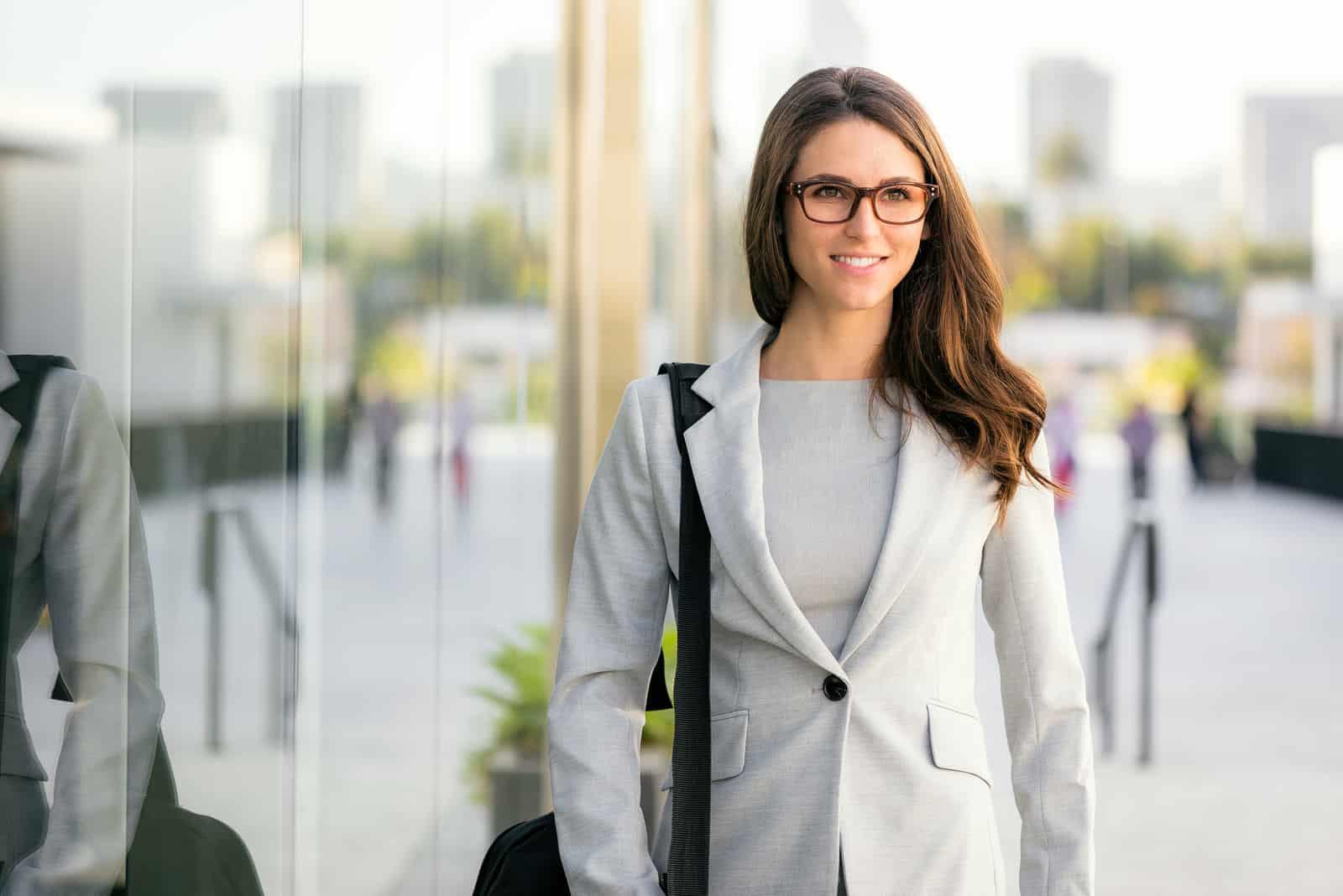 Une femme aux longs cheveux bruns avec un manteau gris marche dans la rue