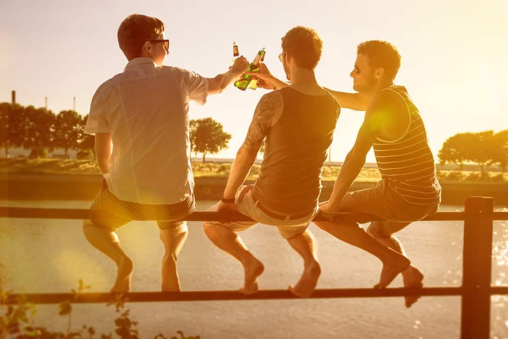 des amis s'assoient sur un banc et portent un toast