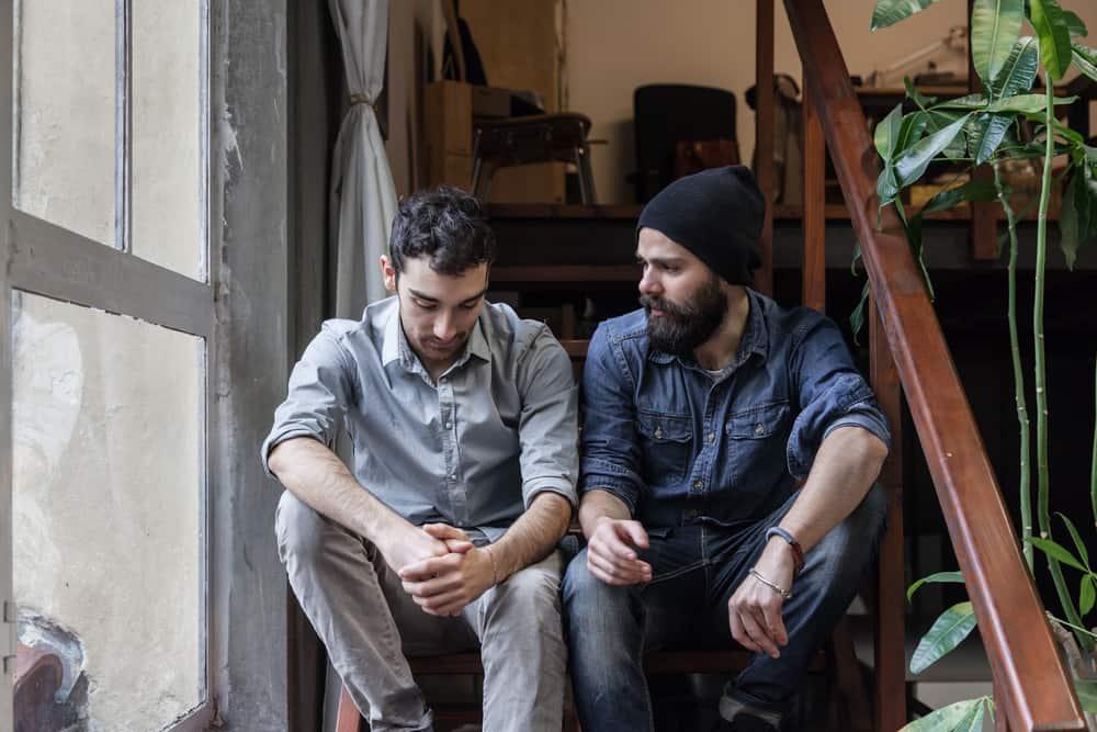 deux hommes s'assoient dans les escaliers et parlent