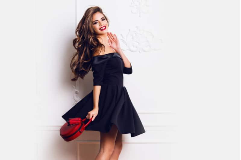 femme séduisante en élégante robe de soirée noire posant sur un mur blanc