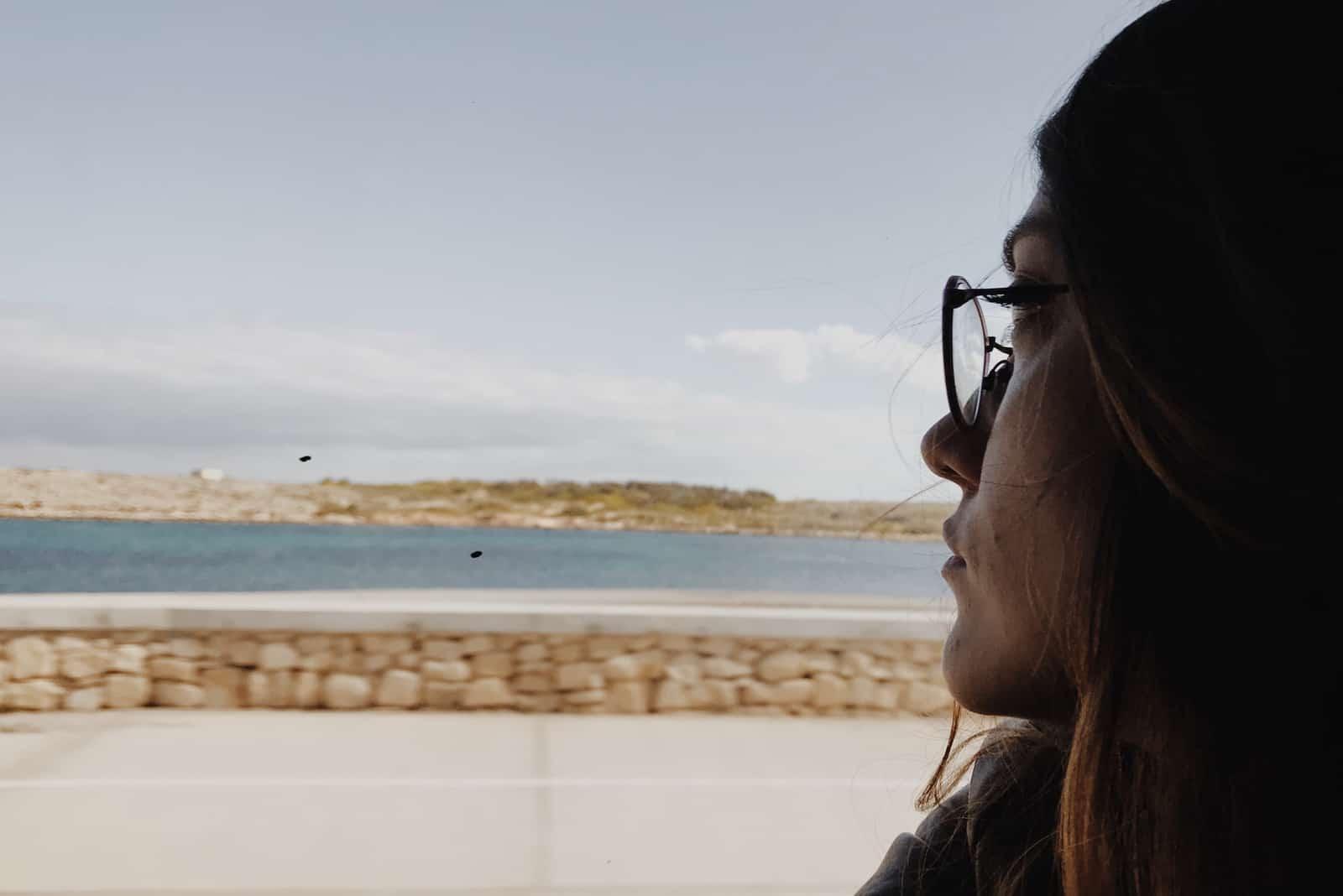 fille triste à travers la fenêtre de la voiture en regardant la mer