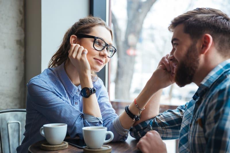 jeune beau couple à une date, boire du café au café