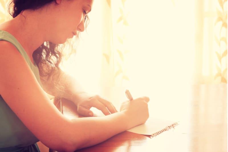jeune femme assise près de la fenêtre et écrit