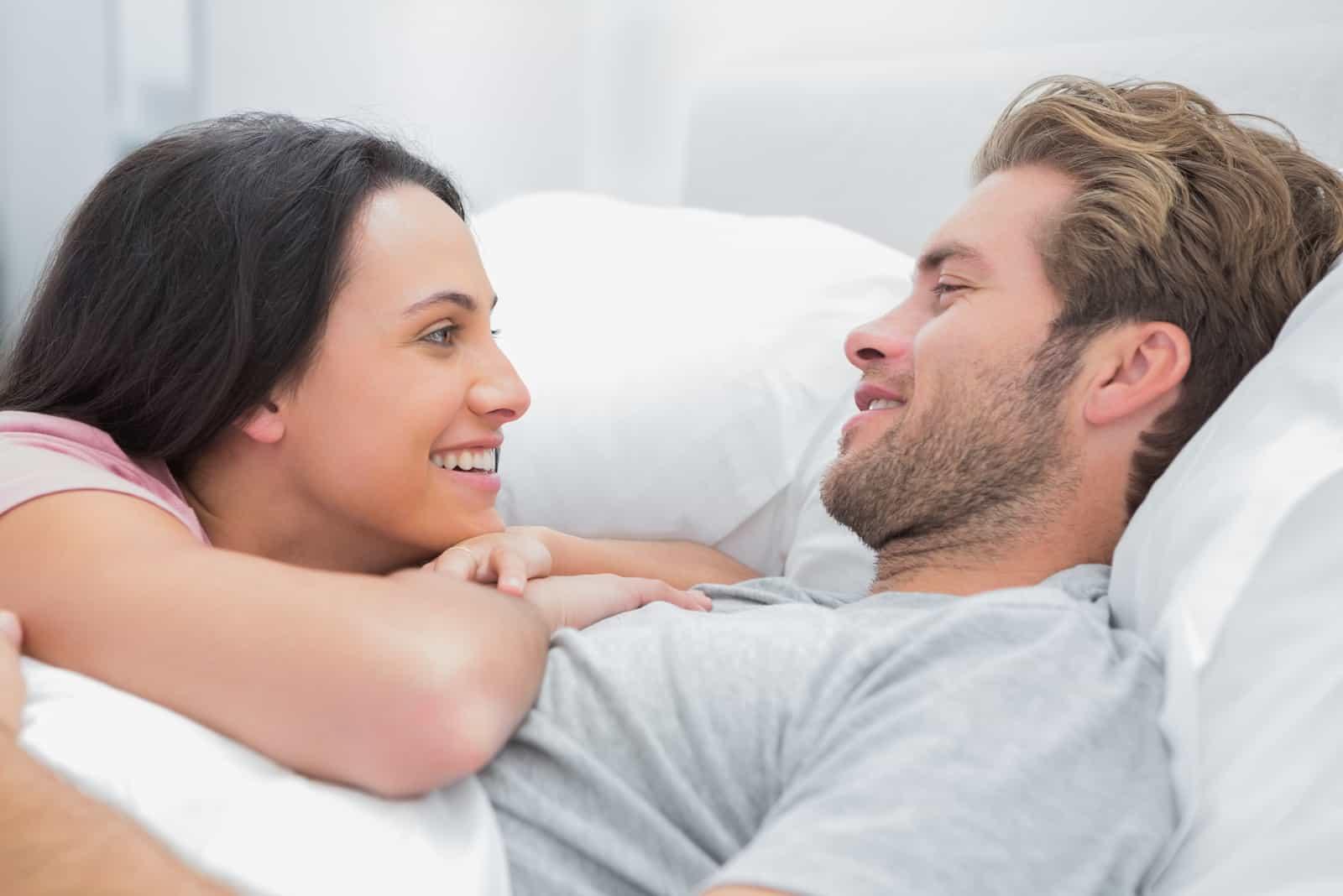 la femme est allongée sur la poitrine de l'homme et ils parlent
