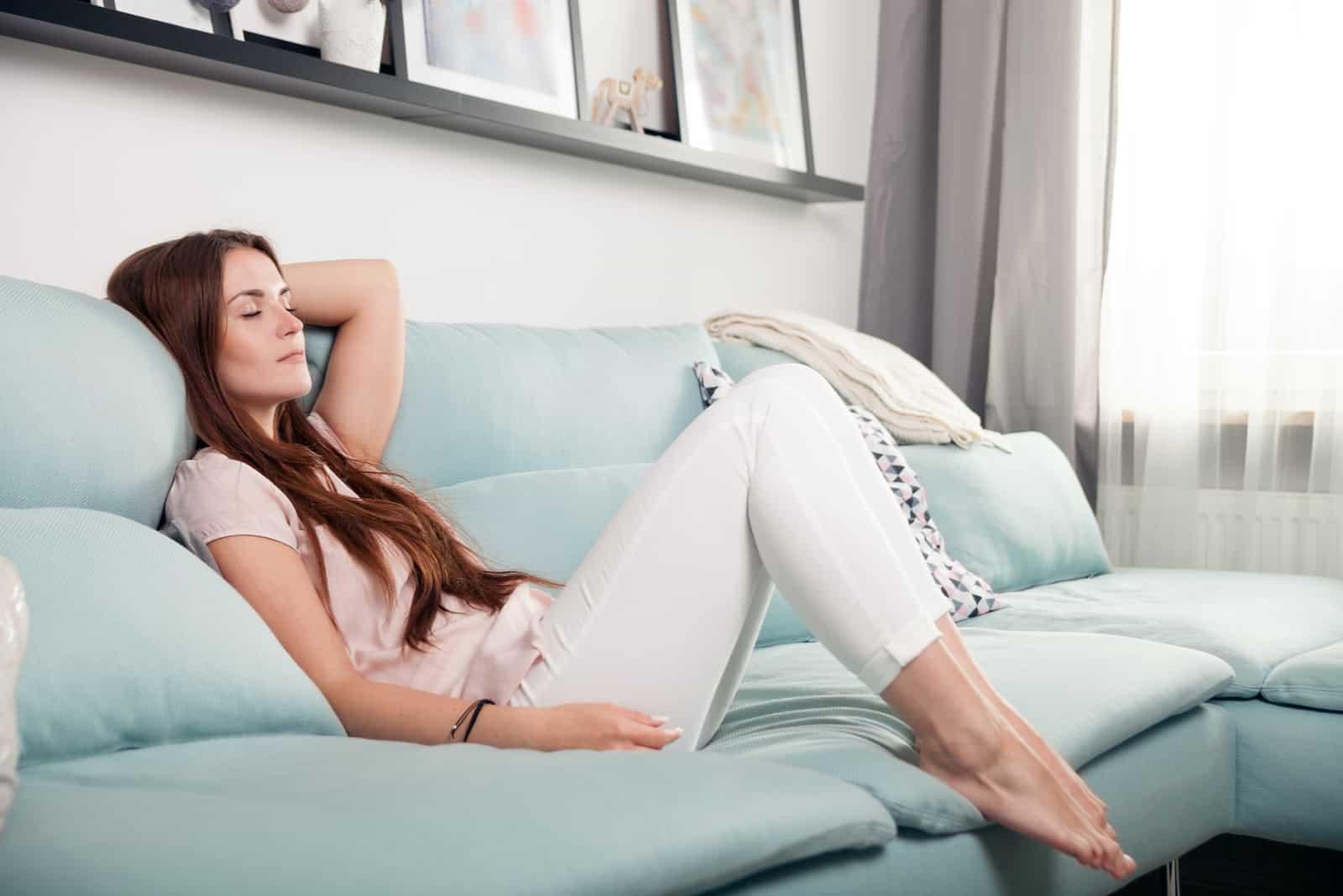 la femme est allongée sur le canapé