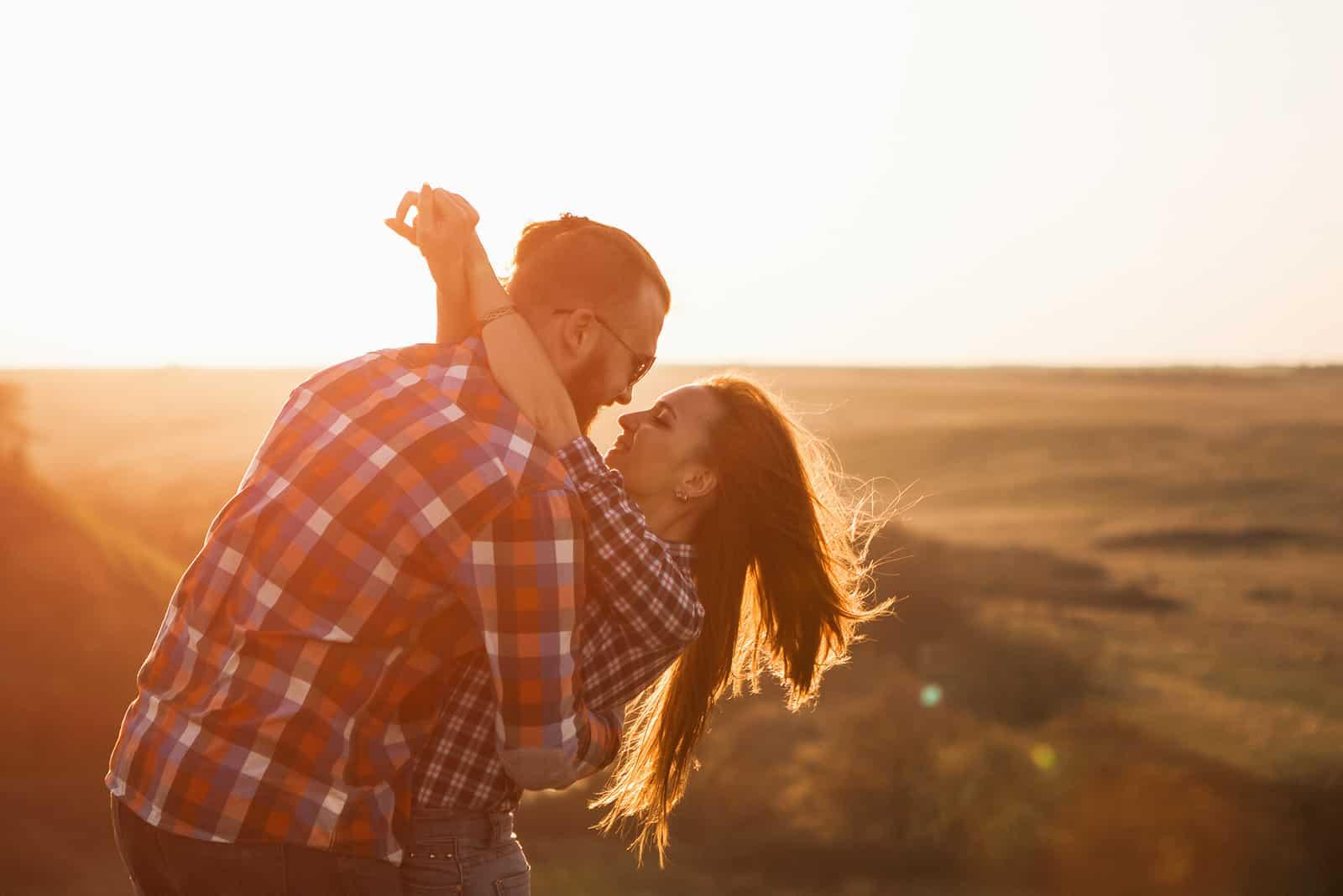 l'homme embrasse la femme sur le terrain et rit