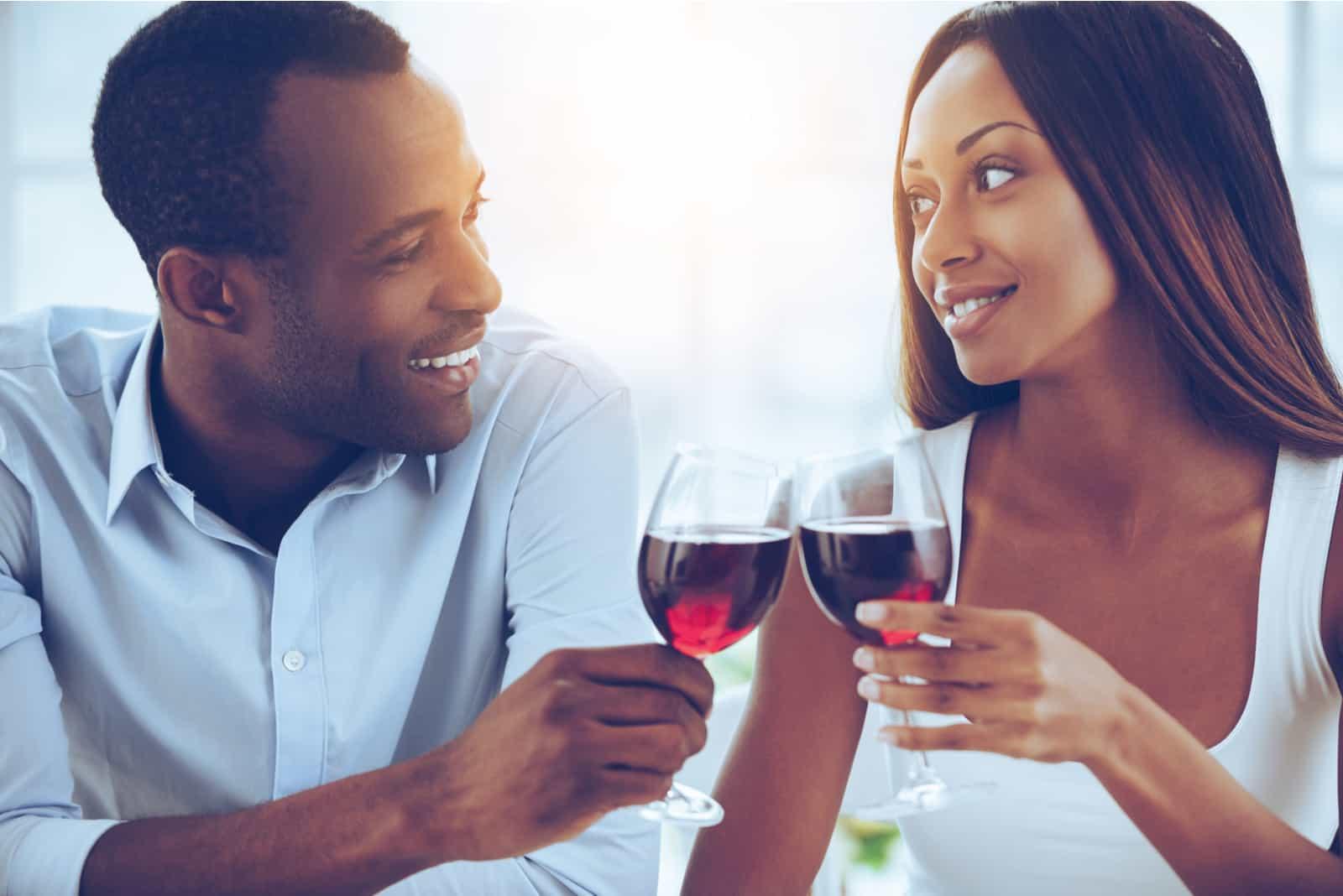l'homme et la femme trinquent avec du vin et rient