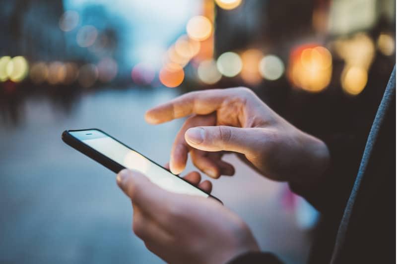 mage de mains mâles à laide de smartphone la nuit