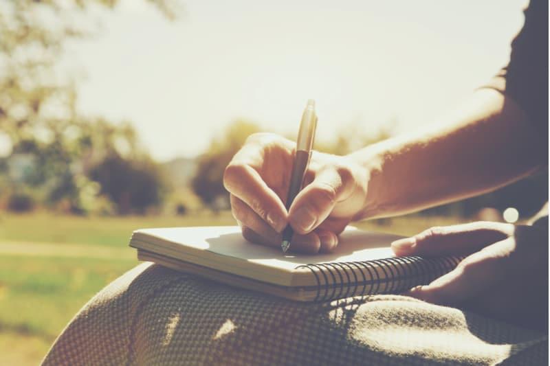mains de filles avec stylo écrit sur ordinateur portable dans le parc