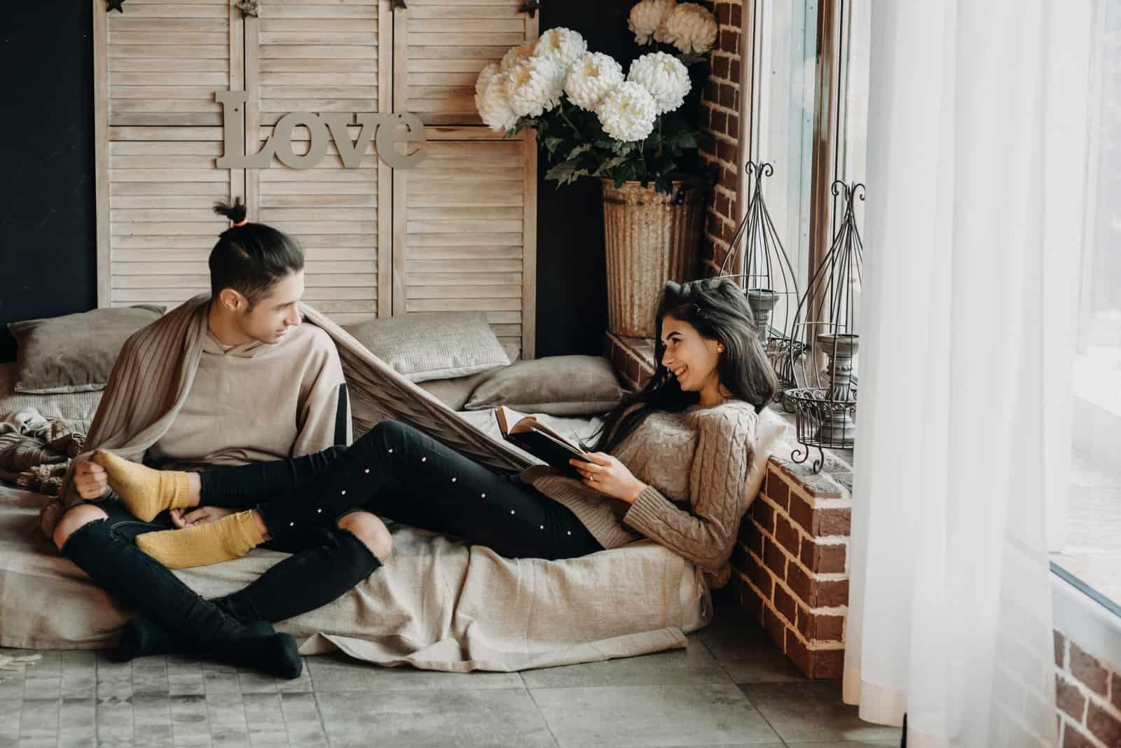 un couple d'amoureux heureux assis dans la maison et s'amuser