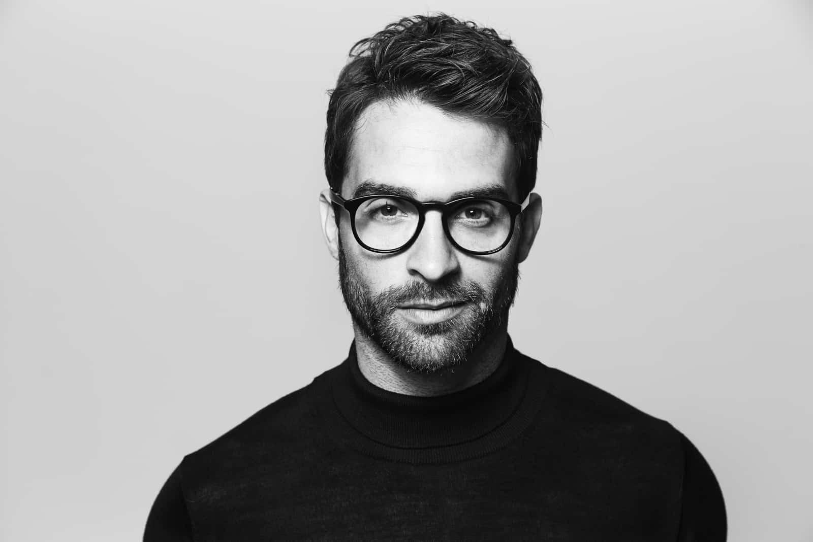 un homme avec des lunettes debout