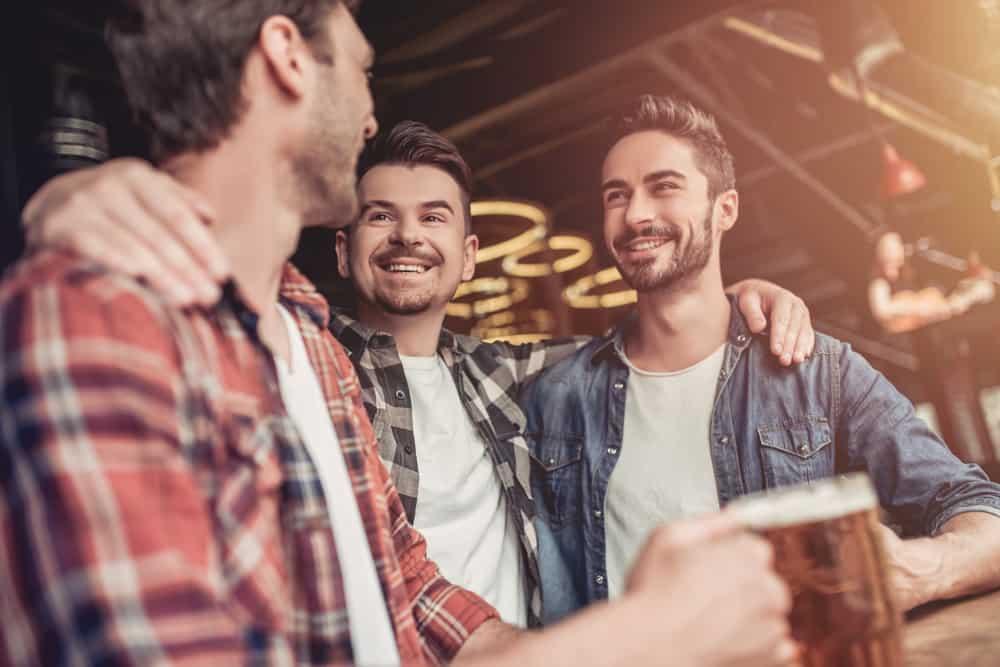 un homme buvant de la bière avec des amis