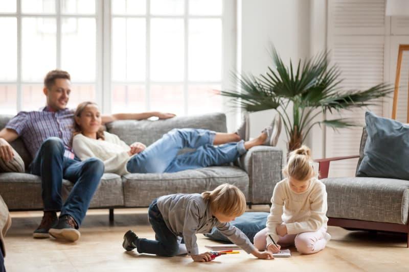 un homme et une femme allongés sur le canapé jouent des enfants