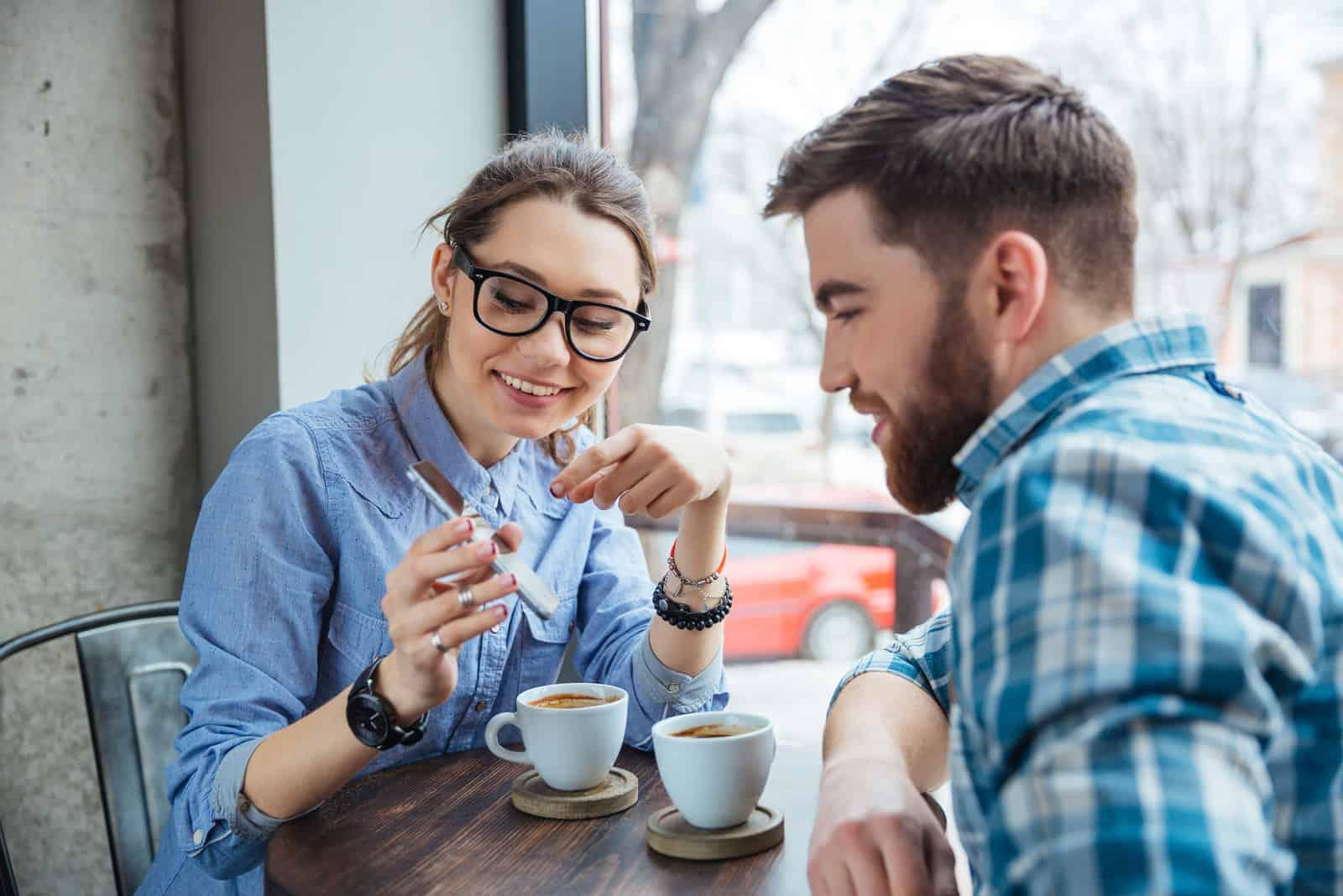 un homme et une femme boivent du café pendant qu'elle pointe quelque chose sur son téléphone