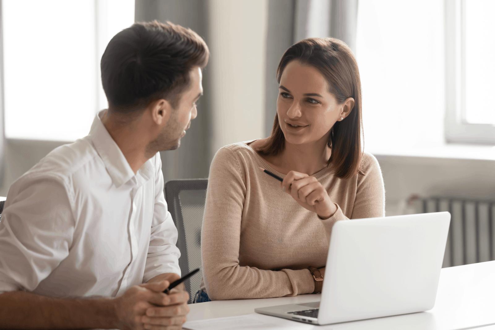 un homme et une femme parlant assis devant un ordinateur portable