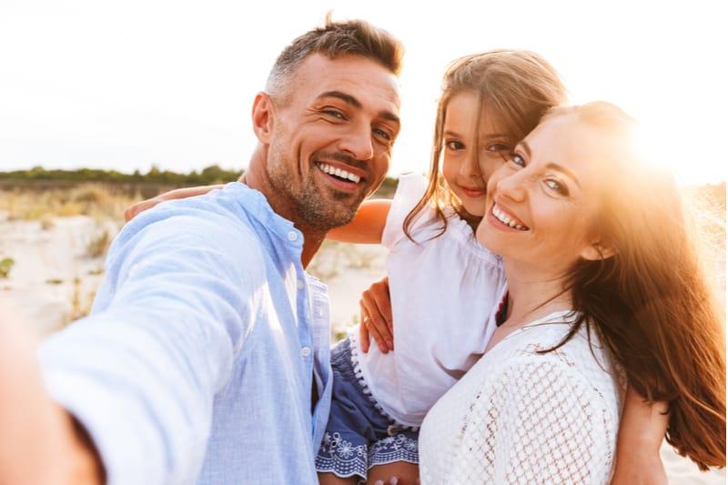 un homme et une femme prennent des photos avec une fille