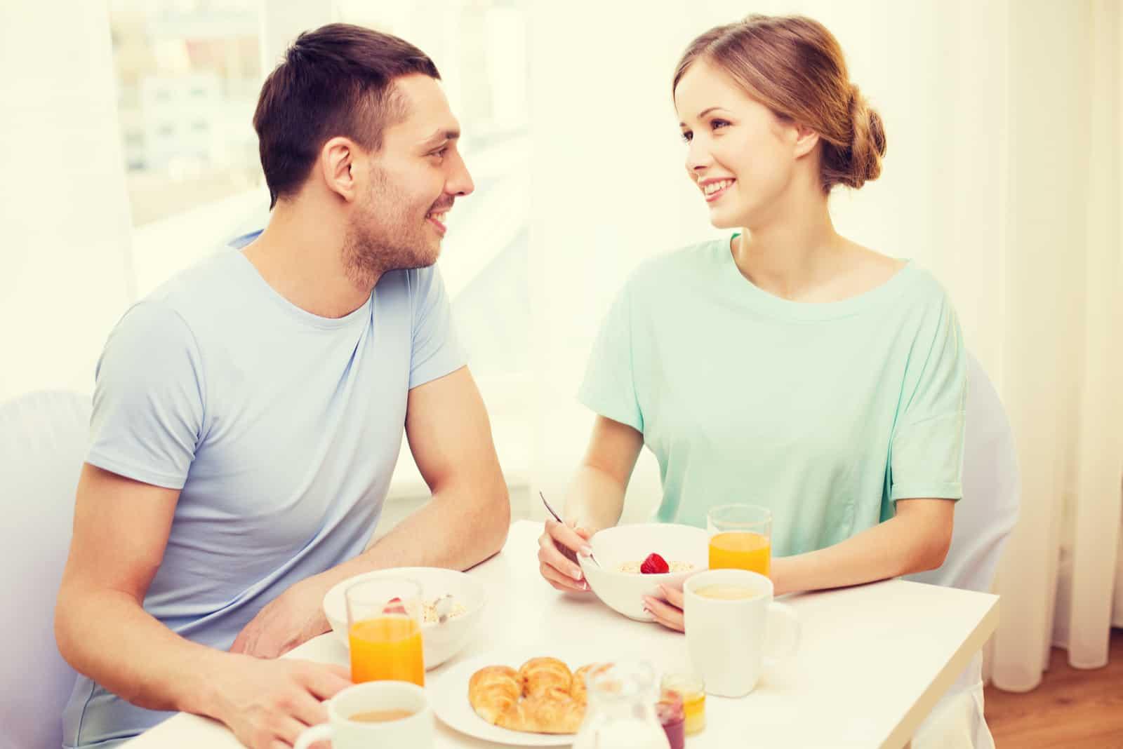 un homme et une femme prennent le petit déjeuner et parlent