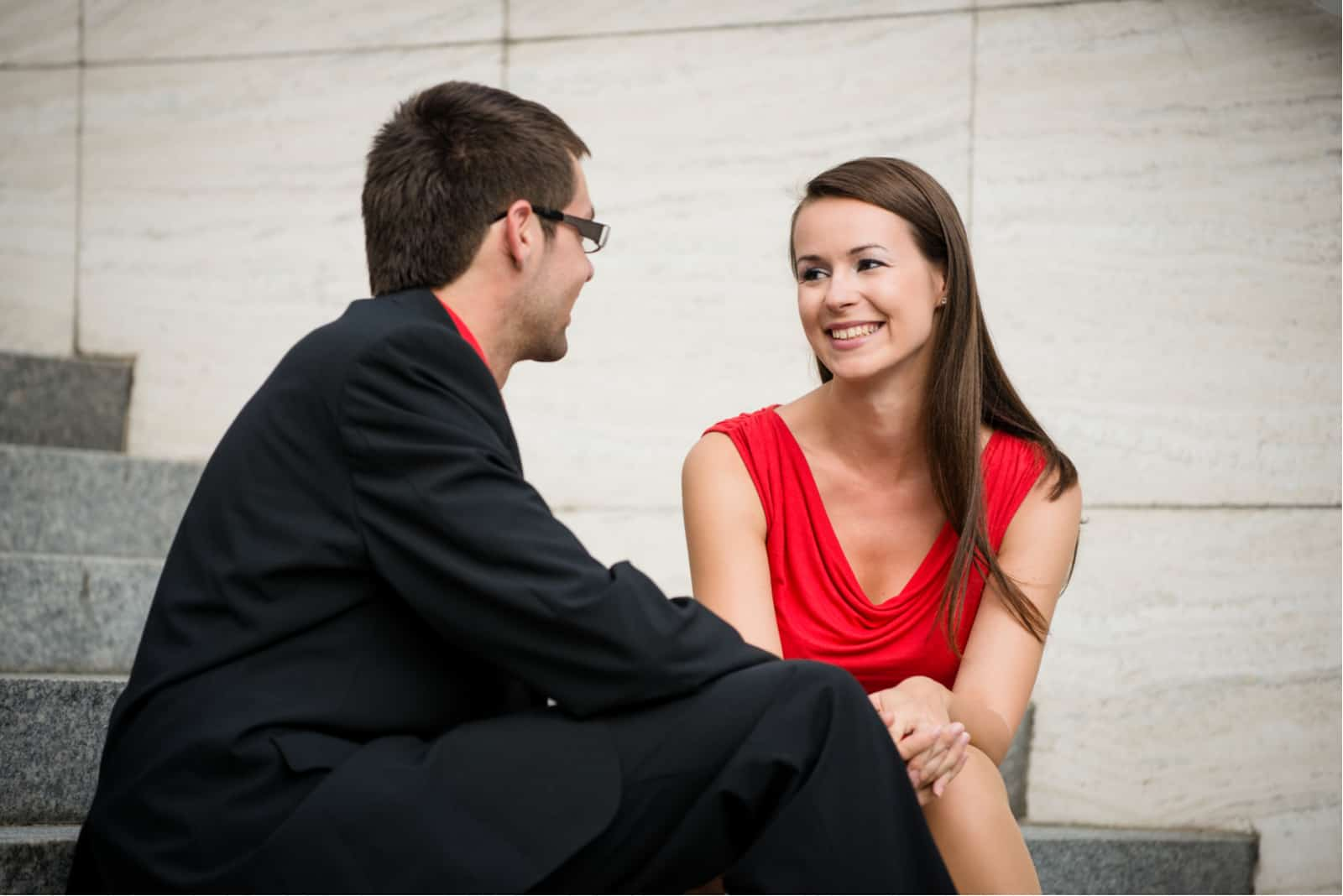 un homme et une femme s'assoient dans les escaliers et rient