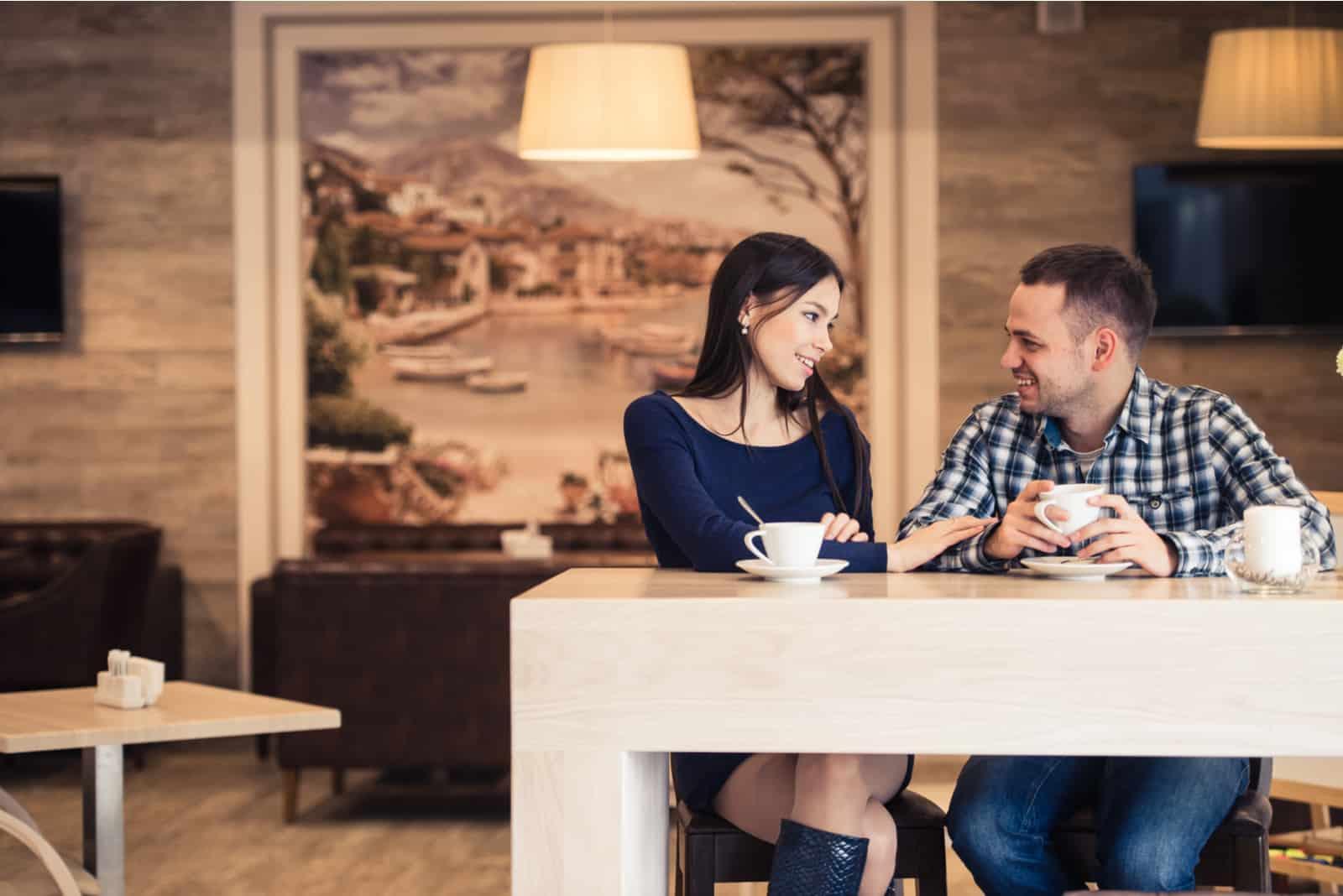 un homme et une femme s'assoient et boivent du café
