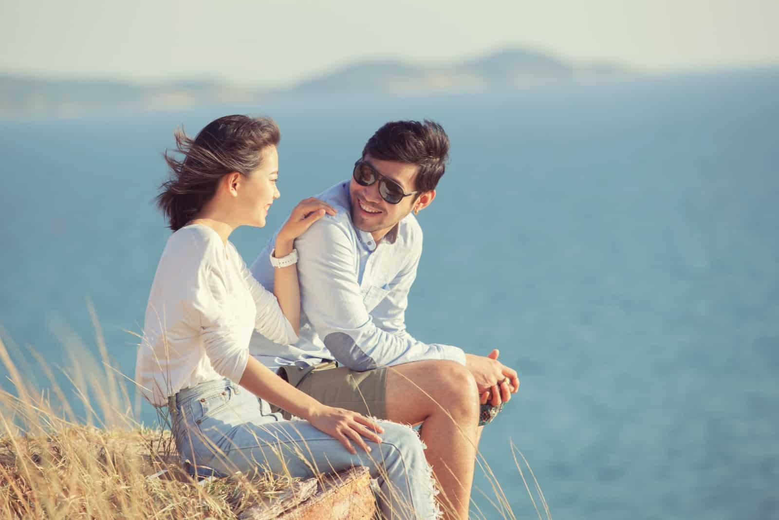 un homme et une femme s'assoient sur un rocher et parlent