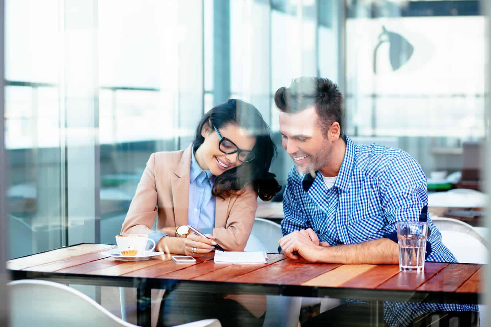 un homme et une femme sont assis à une table pendant qu'elle écrit quelque chose et rit